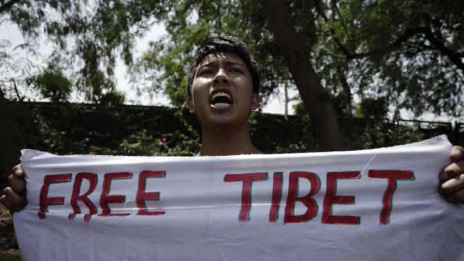 A Tibetan youth activist holds a banner and shouts slogans near the Taj Hotel where the  visiting Chinese premier Li Keqiang, is staying in New Delhi, India, Monday, May 20, 2013. Just weeks after a tense border standoff, China's new premier is visiting India on his first foreign trip as the neighboring giants look to speed up efforts to settle a decades-old boundary dispute and boost economic ties. (AP Photo/Tsering Topgyal)
