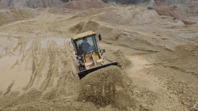 A labourer operates a bulldozer at a site of a rare earth metals mine at Nancheng county, Jiangxi province