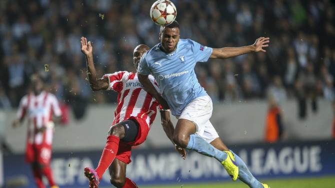 Malmo's Isaac Kiese Thelin heads the ball in front of Olympiakos Piraeus' Eric Abidal during their Champions League soccer match in Malmo