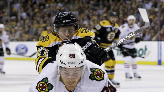 Boston Bruins defenseman Torey Krug (47) checks Chicago Blackhawks right wing Ben Smith (28) to the ice during the first period in Game 3 of the NHL hockey Stanley Cup Finals in Boston, Monday, June 17, 2013. (AP Photo/Elise Amendola)