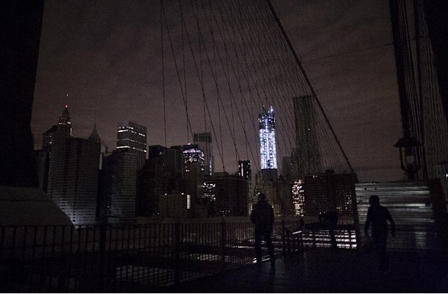 Much of lower Manhattan remains dark, as viewed from the darkened Manhattan side of the pedestrian walkway of the Brooklyn Bridge, Thursday, Nov. 1, 2012 in New York. In the wake of superstorm Sandy,