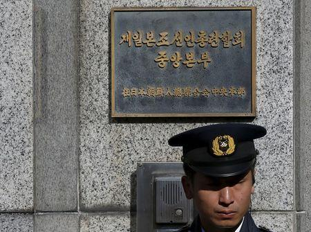 A police officer stands guard at the entrance to the headquarters of the General Association of Korean Residents in Japan, after North Korea's long-range rocket launch, in Tokyo, Japan