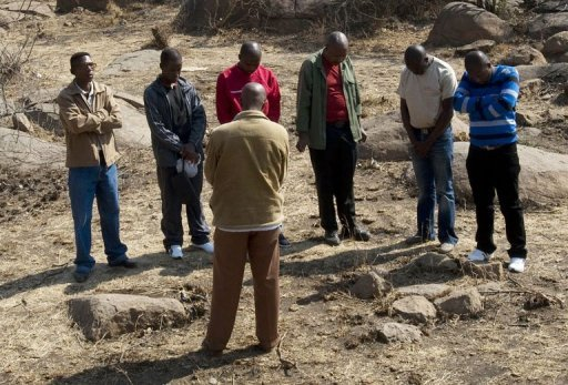 <p>A group of men pray at the site of the death of one of the 34 striking miners who were killed by police near the Lonmin mine in Marikana. Hundreds of striking miners marched Wednesday on the Lonmin Marikana mine in South Africa, as workers accused police of shooting their colleagues in cold blood during a crackdown that killed 34.</p>