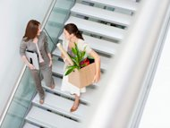woman carrying box of belongings down stairs with another woman