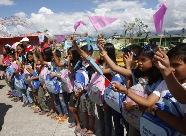 Typhoon survivors wave miniature flags to Australian Foreign Affairs Minister Julie Bishop in Ormoc city in central Philippines