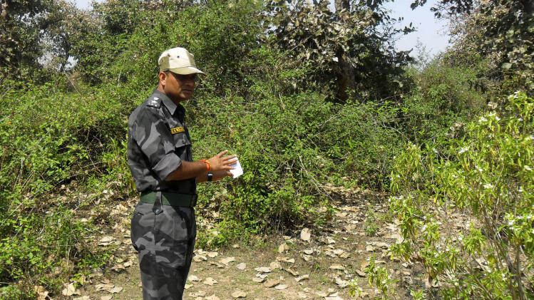 A security officer inspects the site where a Swiss woman was reportedly gang raped by a group of eight men while touring by bicycle with her husband, near Orchcha, in the central Indian state of Madhya Pradesh, Saturday, March 16, 2013. Authorities detained and questioned 13 men in connection with the latest attack, which occurred Friday night as the couple camped out in a forest in Madhya Pradesh state after bicycling from the temple town of Orchha, local police officer R.K. Gurjar said. (AP Photo)