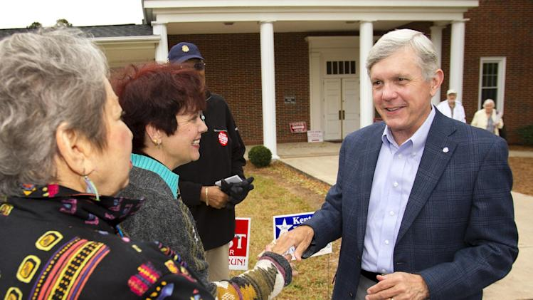 Democratic Lt. Gov. Walter Dalton, right, a candidate for North Carolina governor, greets Judith Abraham, far left, Greensboro City Councilwoman Marikay Abuzuaiter, second from left, and Julius Taylor, outside Muri's Chapel United Methodist Church in Greensboro, N.C., Tuesday, Nov. 6, 2012. Dalton visited at least two polling locations in Greensboro Tuesday morning. (AP Photo/News & Record), Nelson Kepley)