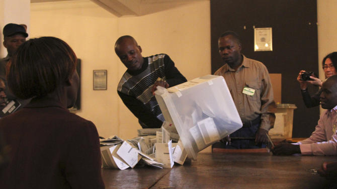 A ballot box is emptied in preparation to count votes after the country went to the polls, Wednesday July 31, 2013 in Harare. Posing one of the biggest threats to President Robert Mugabe's 33-year grip on power, Zimbabweans flocked to polling stations in a presidential election that will determine the course of this southern African country even as suspicions were high that vote-counting could be rigged. (AP Photo)