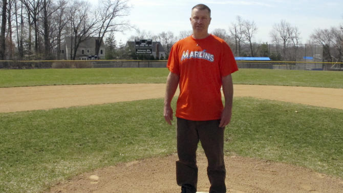 In this April 6, 2015 photo, Christopher Stefanoni poses at the Darien Little League park in Darien, Conn., Stefanoni is suing the Darien Little League in federal court, saying league officials demoted his 9-year-old son to a lower-level team as retribution for his affordable housing proposal. Lawyers for the Little League deny the allegations. (AP Photo/Dave Collins)
