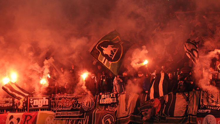 Germany's Hannover 96 supporters wave flags and hold flares during the group B Europa League soccer match against Belgium's Standard Liege, in Liege, Belgium, Wednesday, Nov. 30, 2011. (AP Photo/Geert Vanden Wijngaert)