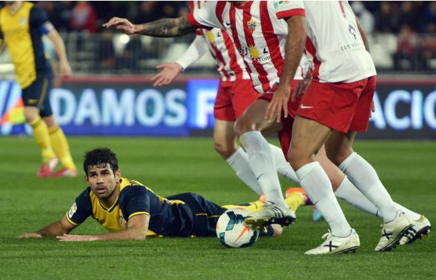 Atletico Madrid's Costa lies on the pitch next to Almeria's players during their soccer match in Almeria