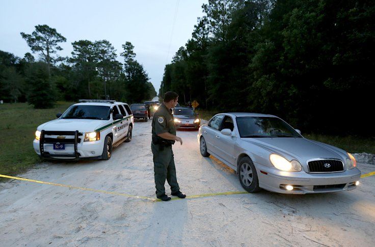 Investigators leave the scene Thursday of an eight-person murder-suicide in rural Florida. (AP Photo/The Gainesville Sun, Matt Stamey)