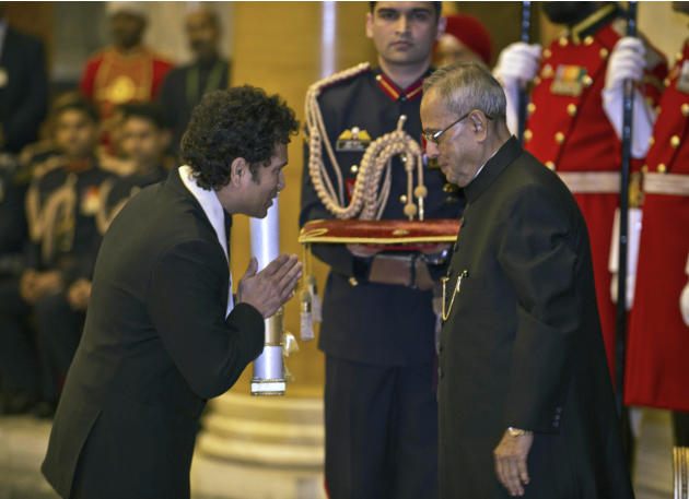 "India's cricket icon Sachin Tendulkar, left, gestures after receiving the ""Bharat Ratna"" award from President Pranab Mukherjee during an awards ceremony at the Presidential Palace in New"