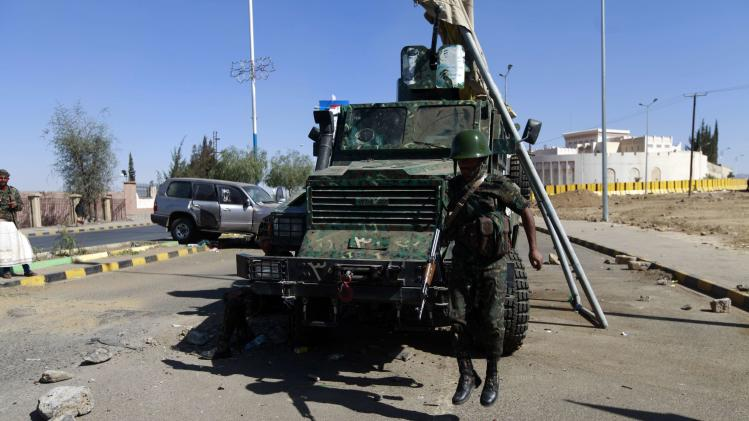 A soldier jumps off an armoured military vehicle near the British embassy in Sanaa