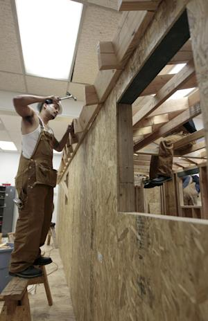 Student Daniel Macias, left, works on building a model house during Project Build class at JobTrain in East Palo Alto, Calif., Thursday, Feb. 23, 2012. As hundreds of employees at Facebook's new headquarters wonder how to spend their millions when the company goes public, the city just up the road has different problems. (AP Photo/Jeff Chiu)