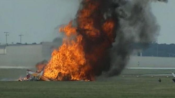 This photo provided provided WHIO TV shows a plane after it crashed Saturday, June 22, 2013, at the Vectren Air Show near Dayton, Ohio. There was no immediate word on the fate of the pilot, wing walker or anyone else aboard the plane. No one on the ground was hurt. (AP Photo/WHIO-TV)