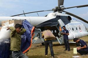 Nepalese villagers load relief materials onto a helicopter …
