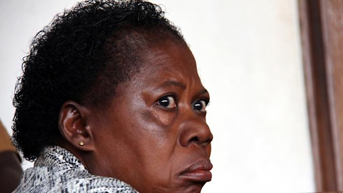 """In this photograph taken on Thursday, March 20, 2014, a Ugandan nurse, Rosemary Namubiru, sits in court in the capital Kampala, Uganda. She is accused of injecting a two year old boy Mathew Mushabe with HIV/Aids virus. Goaded by journalists who wanted a clear view of her face, the Ugandan nurse looked dazed and on the verge of tears. The Ugandan press had dubbed her """"the killer nurse"""" after the HIV-infected medical worker was accused of deliberately injecting her blood into a two-year-old patient. (AP Photo)"""