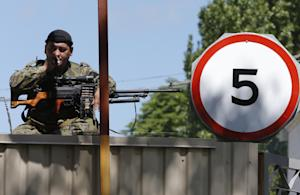 A pro-Russian fighter smokes as he guards an entrance…