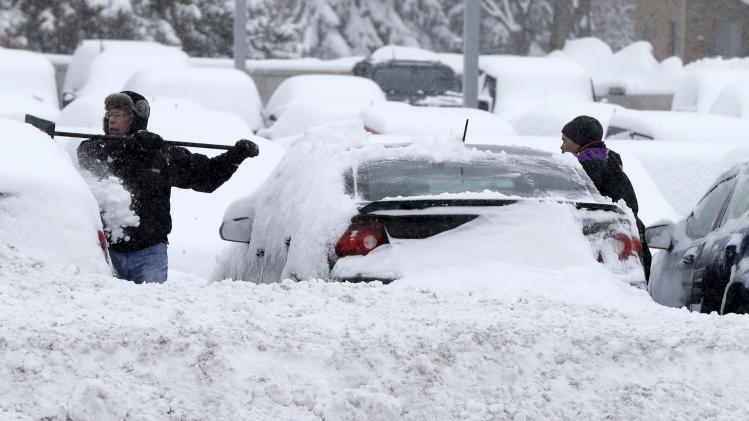 Workers remove snow from cars at an auto dealership Tuesday, March 5, 2013, in Bloomington, Minn. left by a storm that is crawling east from the Dakotas and Minnesota toward Chicago which could bring up to 10 inches of snow in some areas. (AP Photo/Jim Mone)