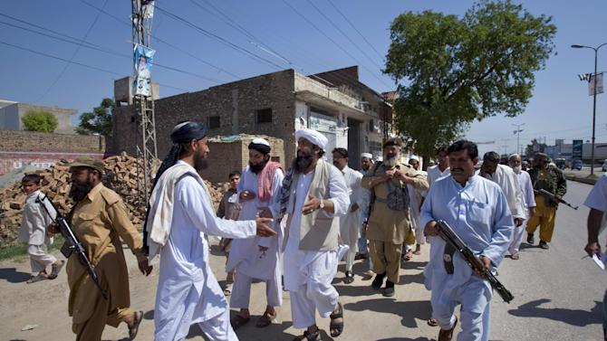 """In this Thursday, May 2, 2013 photo, Maulana Shujaul Mulk, center, pro-Taliban Jamiat-e-Ulema Islam (JUI-F), surround by guards as he greets a supporter during his election campaign at a road in Mardan, Pakistan. Mulk is among several Pakistani Islamists and sectarian groups contesting for the country's upcoming parliamentary elections, which are divided and scattered though, they are still in a position to secure enough strength to play Pakistani establishment bid to """"hound"""" the next frail government in influencing its decisions about the U.S. forces withdrawal from Afghanistan in 2014. (AP Photo/Anjum Naveed)"""