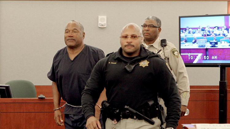 O.J. Simpson,left, is escorted by Rik Moon, Clark County Marshal and Las Vegas Police correctional  officer George Gafford, right, during a break in his evidentiary hearing testimony in Clark County District Court, Wednesday, May 15, 2013 in Las Vegas. Simpson, who is currently serving a nine to 33-year sentence in state prison as a result of his October 2008 conviction for armed robbery and kidnapping charges, is using a writ of habeas corpus, to seek a new trial, claiming he had such bad representation that his conviction should be reversed. (AP Photo/Las Vegas Review-Journal, Jeff Scheid, Pool)