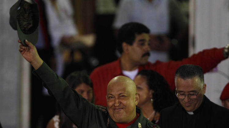 Venezuela's President Hugo Chavez greets hi supporters upon his arrival to the Miraflores presidential palace after his third round of chemotherapy, in Caracas, Venezuela, Friday Sept. 2, 2011. The 57-year-old president, who shaved his head after he started losing hair due to the treatments, did jumping jacks and sparred as he left the Carlos Arvelo Military Hospital in Venezuela's capital. (AP Photo/Fernando Llano)