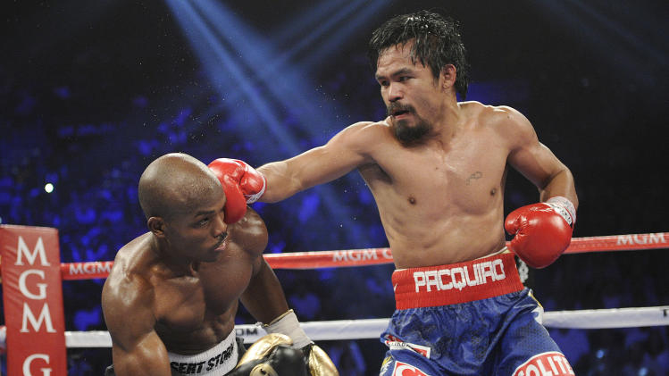 Manny Pacquiao, right, from the Philippines, connects with a right to the head of Timothy Bradley, from Palm Springs, Calif., in their WBO world welterweight title fight Saturday, June 9, 2012, in Las Vegas. (AP Photo/Chris Carlson)