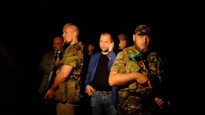 """Self-proclaimed Prime Minister of the pro-Russian separatist """"Donetsk People's Republic"""" Alexander Borodai (C) stands as he arrives on the site of the crash of a malaysian airliner carrying 298, in rebel-held east Ukraine, on July 17, 2014"""