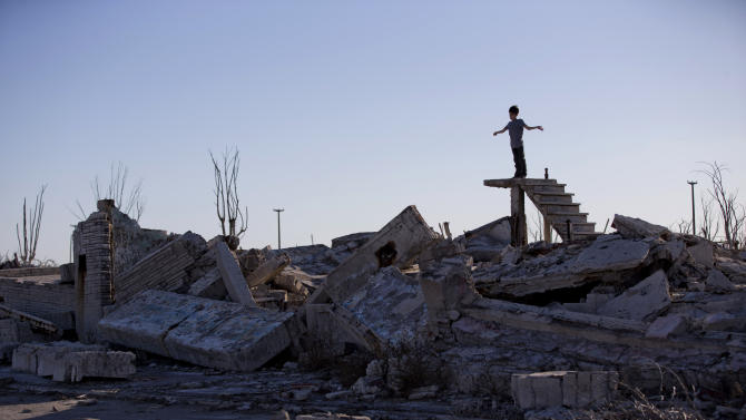 In this May 6, 2013 photo, a young tourist stands on stairs protruding from the rubble of homes in Epecuen, which once was submerged in water in Argentina. When a particularly heavy rainstorm followed a series of wet winters, the lake overflowed its banks on Nov. 10, 1985. Water burst through a retaining wall and submerged the lakeside streets. People fled with what they could, but a few days later, their homes were drowned under nearly 10 meters (33 feet) of corrosive saltwater. (AP Photo/Natacha Pisarenko)