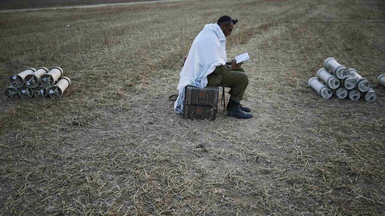 Israeli soldier prays in a field near the central Gaza Strip