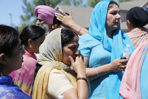 Bystanders stand outside the scene of a shooting inside The Sikh Temple in Oak Creek, Wis, Sunday, Aug. 5, 2012. Police in Wisconsin say at least seven people are dead at a Sikh temple near Milwaukee, including the suspected gunman. (AP Photo/Jeffrey Phelps)