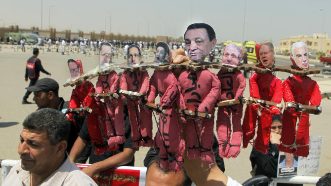 Egyptian anti-Mubarak protesters hold effigies representing former Egyptian President Hosni Mubarak, center, his wife Suzanne, fourth left, and his sons Gamal, third left, and Alaa, second left,  outside a court in Cairo, Egypt, Saturday, May 11, 2013. Egyptian prosecutors say they are presenting new evidence in the retrial of former President Hosni Mubarak for failing to stop the killing of 900 protestors in the 2011 unrest that ousted him. The sons face corruption charges. (AP Photo/ Amr Nabil)