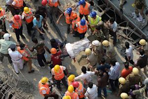 Indian rescue workers carry away a body next to the…