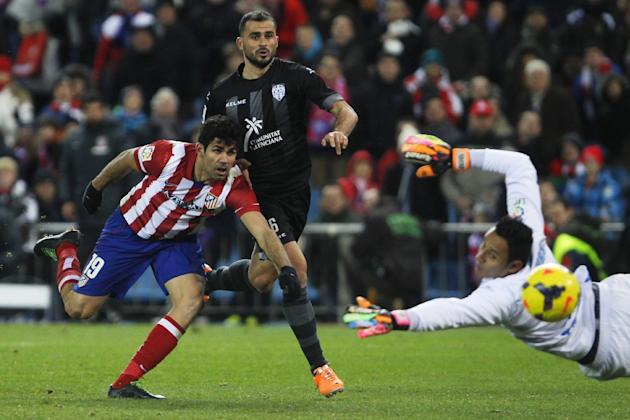 Atletico's Diego Costa, left, misses a chance after shooting past goalkeeper Keylor Navas from Costa Rica during a Spanish La Liga soccer match between Atletico de Madrid and Levante at the Vicent