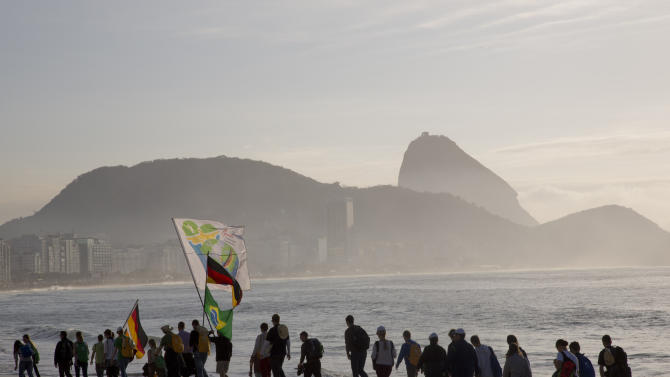 Backdropped by Sugar Loaf mountain, a group walks along the Copacabana beach on their way to attend the World Youth Day's closing Mass, in Rio de Janeiro, Brazil, Sunday, July 28, 2013. An estimated 3 million people poured onto Rio's Copacabana beach on Sunday for the final Mass of Pope Francis' historic trip to his home continent, cheering the first Latin American pope in one of the biggest turnouts for a papal Mass in recent history. (AP Photo/Andre Penner)