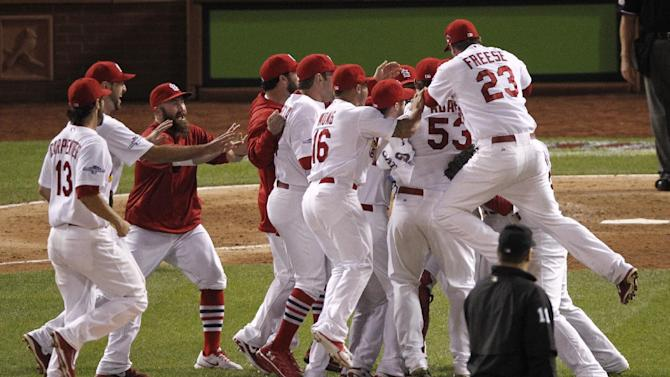 The St. Louis Cardinals celebrate after beating the Pittsburgh Pirates 6-1 in Game 5 of a National League baseball division series, Wednesday, Oct. 9, 2013, in St. Louis. The Cardinals advanced to the NL championship series against the Los Angeles Dodgers