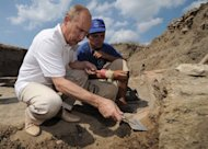 Russian Prime Minister Vladimir Putin (left) cleans an ancient amphora as he visits a site of archaeological excavations on the Taman Peninsula. Putin pulled on a wetsuit and went scuba diving at an ancient Greek Black Sea site in the latest populist stunt preceding next year's elections