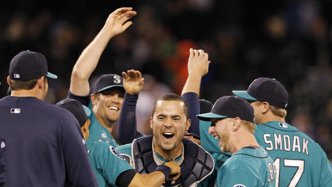 Seattle Mariners catcher Jesus Montero, center, celebrates with teammates, including closer Tom Wilhelmsen, left, after the final out against the Los Angeles Dodgers in a baseball game Friday, June 8, 2012, in Seattle. The Mariners won 1-0 in a six-pitcher combined no-hitter. (AP Photo/Elaine Thompson)