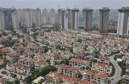 A block of villa residences is seen in front of new residential buildings under construction in Shenyang, Liaoning province