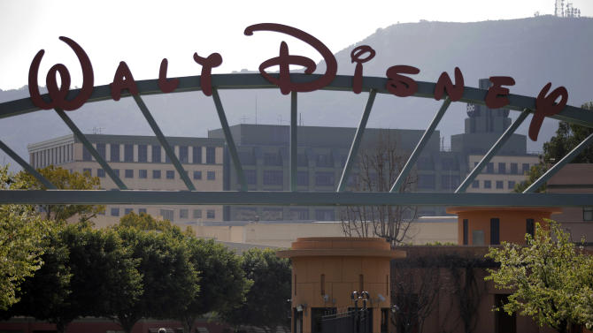 People stand near the entrance to the Walt Disney Studios is seen in Burbank , Calif., Tuesday, Feb. 8, 2011. Walt Disney Co. releases quarterly financial earnings Tuesday, after the market close.(AP Photo/Jae C. Hong)