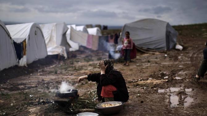 A Syrian woman who fled her home cooks for her family outside her tent at a camp for displaced Syrians in the village of Atmeh, Syria, Tuesday, Dec. 11, 2012. This tent camp sheltering some of the hundreds of thousands of Syrians uprooted by the country's brutal civil war has lost the race against winter: the ground under white tents is soaked in mud, rain water seeps into thin mattresses and volunteer doctors routinely run out of medicine for coughing, runny-nosed children. (AP Photo/Muhammed Muheisen)