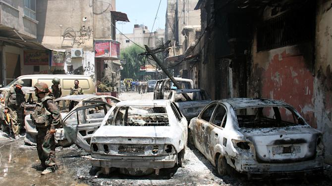 In this photo taken during a government-organized tour, Syrian soldiers stand next to burned cars after they regained control of the district of Midan, in the southern part of Damascus, Syria, Friday, July 20, 2012. Syrian troops and tanks on Friday drove rebels from a Damascus neighborhood where some of the heaviest of this week's fighting in the capital left cars gutted and fighters' bodies in the streets. Hundreds of people were killed in a single day, activists said, as the military struggles to regain momentum after a stunning bombing against the regime's leadership. (AP Photo/Bassem Tellawi)