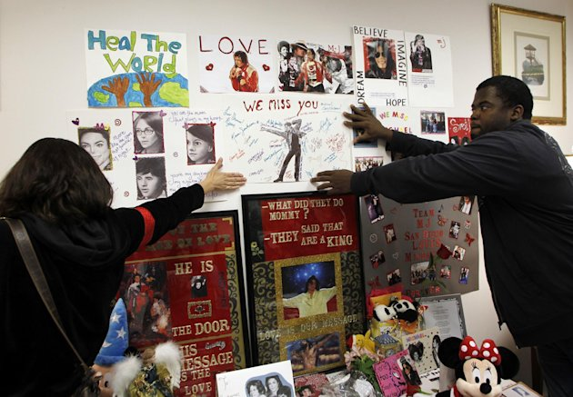 Michael Jackson fans Kim Lemieux, left, and Michael Craig hang a poster at a memorial where the headboard of the bed that Jackson was in on the day he died would have been placed in an exhibition at Julien&#39;s Auctions during a private preview of contents of 100 North Carolwood Drive, the home where Michael Jackson was living when he died, on Sunday, Dec. 11, 2011 in Beverly Hills, Calif. The carved headboard seen in evidence photos during the criminal trial of Jackson&#39;s physician was removed from the auction&#39;s lots at the request of Jackson&#39;s estate. (AP Photo/Danny Moloshok)