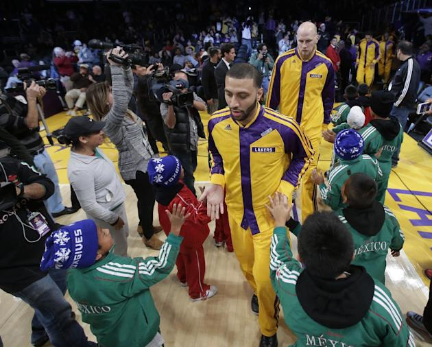 Members of Triqui kids basketball team, made up of children from the mountainous region of Oaxaca, Mexico, greet the Los Angeles Lakers before an NBA basketball game against the Minnesota Timberwolves