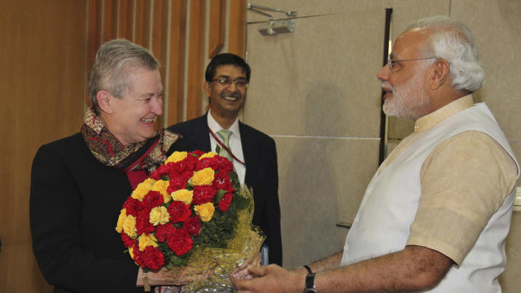 In this photo released by India's Gujarat state government, U.S. Ambassador to India, Nancy Powell, left, receives flowers presented to her by India's opposition Bharatiya Janata Party's prime ministerial candidate Narendra Modi, right, as she visits him at his residence in Gandhinagar, India, Thursday, Feb. 13, 2014. Powell on Thursday met with the Gujarat chief minister for the first time since he was refused a U.S. visa over alleged complicity in deadly anti-Muslim riots in 2002. (AP Photo/Gujarat state government)