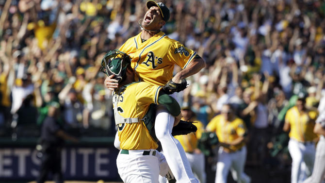 Oct. 3 Oakland Athletics relief pitcher Grant Balfour, top, and catcher Derek Norris celebrate after their 12-5 win over the Texas Rangers in a baseball game, Wednesday, Oct. 3, 2012 in Oakland, Calif. The A's clinch the AL West title with the win. (AP Photo/Ben Margot)