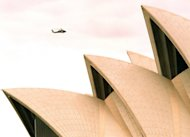This file photo shows a helicopter flying over the Sydney Opera House, on August 11, 1998. A plan for wealthy executives and tourists landing in Sydney to flit directly to the city's famous harbour via a floating heliport has been put on hold after fierce public opposition