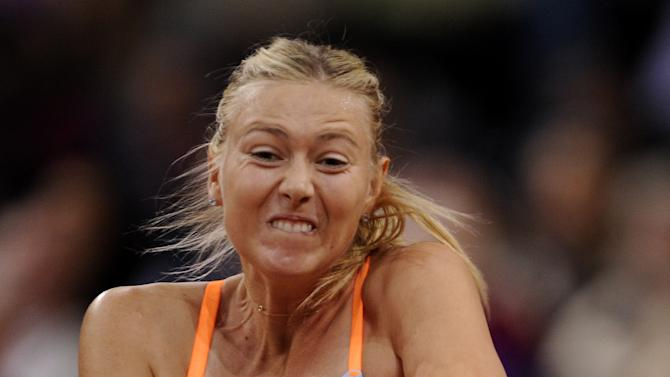 Maria Sharapova from Russia returns a ball to Na Li from China during the final of the WTA tennis Porsche GP in Stuttgart, Germany, Sunday, April 28, 2013. (AP Photo/Daniel Maurer)