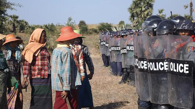 Farmers confront riot police at the site of the Letpadaung copper-mine near Monywa in northwestern Myanmar Monday, Dec. 22, 2014. A woman was fatally shot Monday during a crackdown on protesters at the controversial Chinese-backed copper mine, activists and an opposition lawmaker said. Khin San Hlaing, a lawmaker from the National League for Democracy party, said the confrontation at the Letpadaung copper-mine project, a joint venture between a Myanmar military-controlled holding company and China's Wanbao Mining Copper Ltd., occurred as police and Chinese workers erected a fence on land that the villagers claimed as theirs. (AP Photo)
